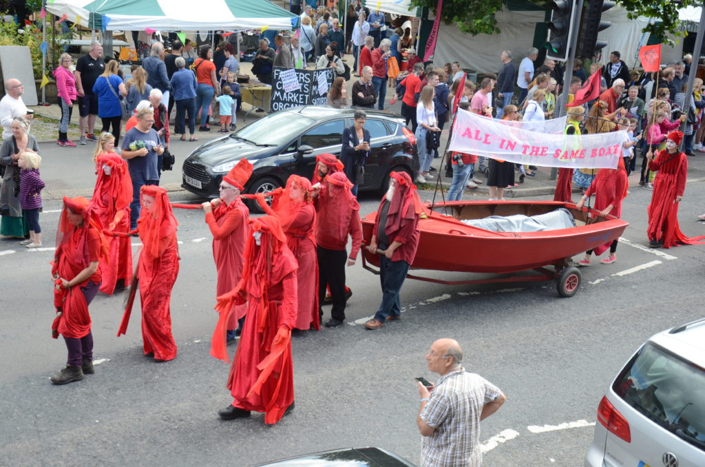 Red boat with banner 'We are all in the same boat' hauled by people dressed in red.